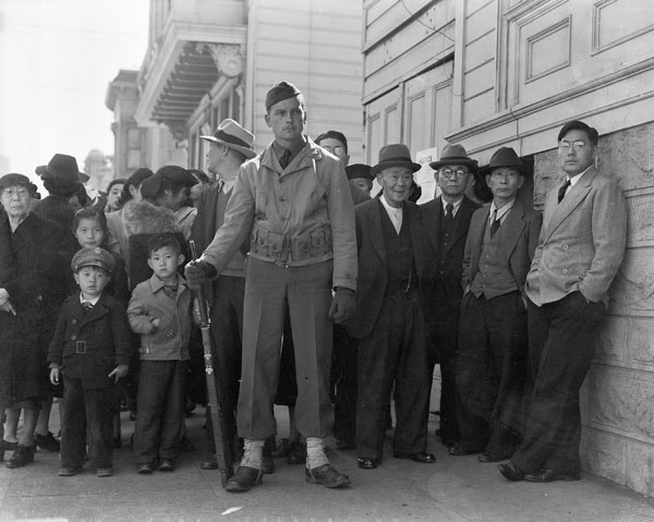 "A crowd of onlookers on the first day of evacuation from the Japanese quarter in San Francisco, who themselves will be evacuated within three days."" By Dorothea Lange, San Francisco, California, April 1942"